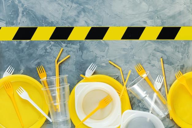 Pratos de plástico e fita de advertência em um fundo cinza. copie o espaço. poluição ambiental.