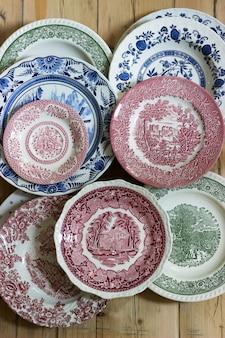 Pratos de porcelana vintage em diferentes tamanhos e cores em uma mesa de madeira. estilo rústico.