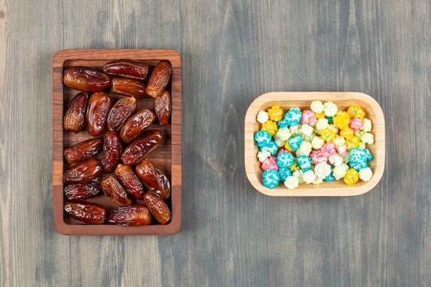 Pratos de tâmaras e pipocas coloridas em superfície de madeira