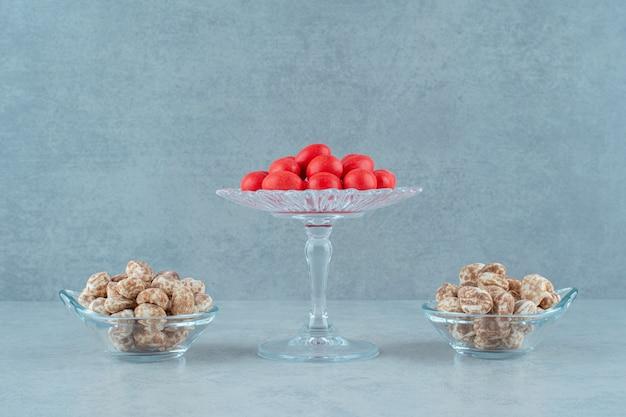 Pratos de vidro cheios de deliciosos biscoitos de gengibre e doces vermelhos na superfície branca