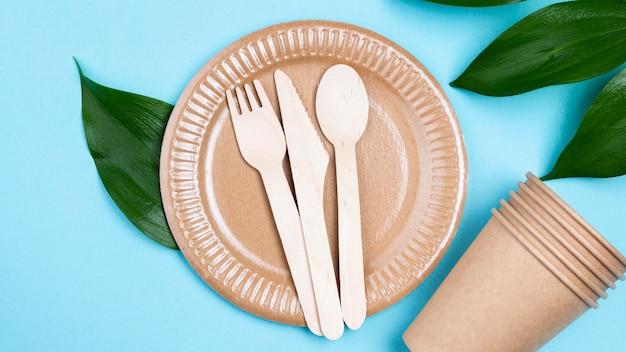 Pratos descartáveis com copos e talheres vista superior