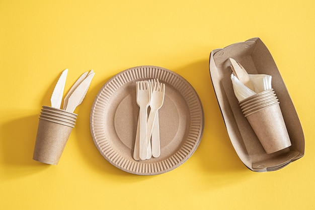 Pratos descartáveis ecológicos feitos de papel em um fundo laranja.