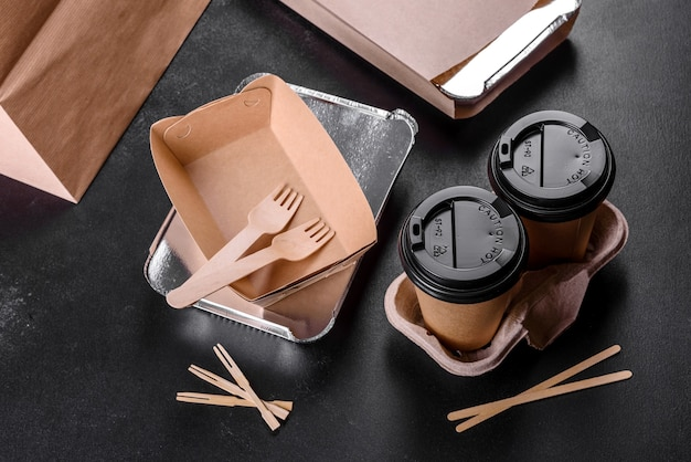 Pratos descartáveis feitos de papelão marrom ecológico sobre fundo escuro. entrega de comida em pratos descartáveis