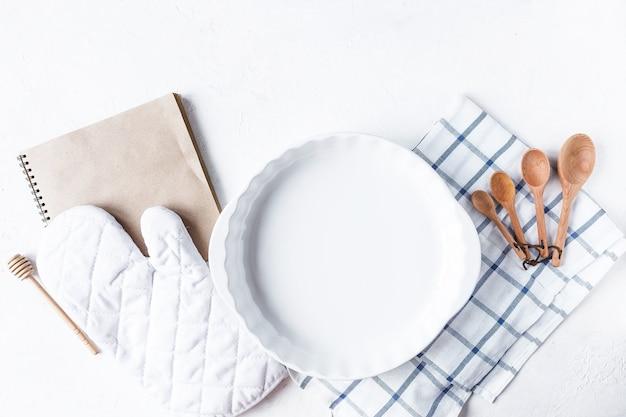 Pratos e acessórios de cozinha para assar na mesa da cozinha em um fundo branco