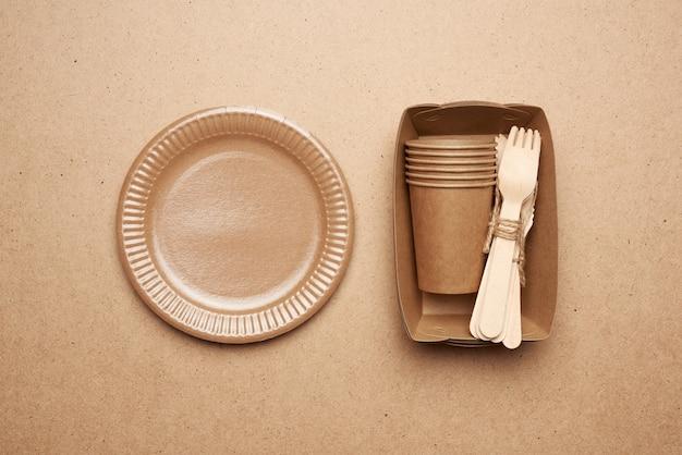 Pratos e copos de papel de papel marrom e garfos de madeira