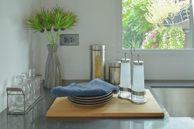 Pratos e garrafas de vidro, definindo na bancada preta na cozinha