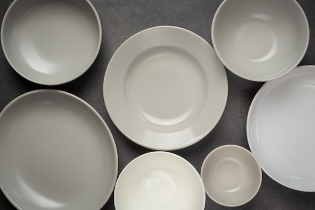 Pratos e tigelas vazios redondos e brancos na superfície escura