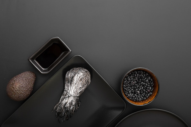 Pratos escuros com feijão e macarrão em um fundo escuro