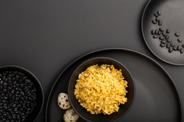 Pratos escuros com feijão e tigela de arroz em uma mesa escura