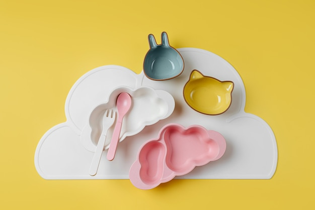 Pratos infantis bonitos sobre fundo amarelo. servindo bebê. conceito de cardápio infantil, nutrição e alimentação