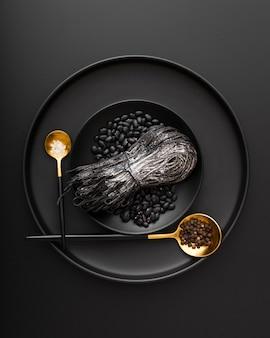 Pratos pretos com macarrão e feijão em um fundo escuro