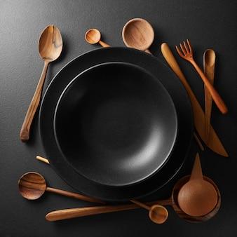 Pratos pretos e colher de pau, garfo, faca em uma mesa preta.