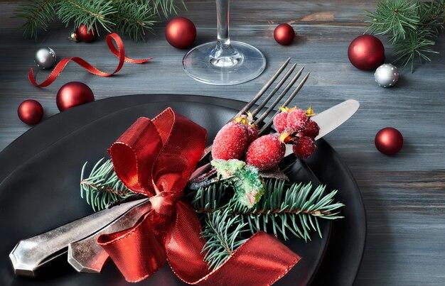 Pratos pretos e talheres com decorações de natal na mesa de madeira