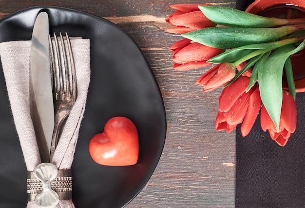 Pratos pretos, guardanapos pretos, talheres vintage com tulipas vermelhas e coração decorativa