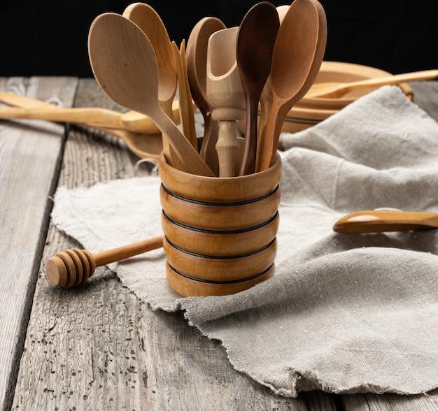 Pratos redondos de madeira vazios e colheres em uma mesa cinza