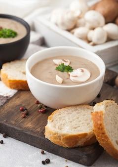 Pratos tigela de cerâmica de sopa cremosa de cogumelos champignon castanha com colher, pimenta e pano de cozinha no fundo branco da cozinha e uma caixa de cogumelos crus.