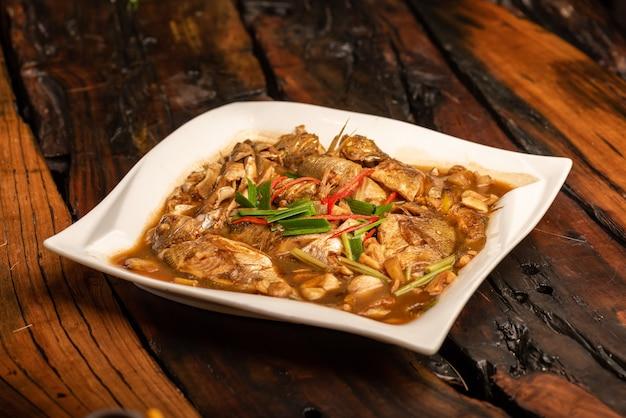 Pratos tradicionais de banquete chinês, peixe do mar cozido com molho amarelo