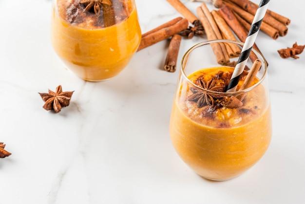 Pratos tradicionais de outono, batido de torta de abóbora picante com canela, anis e aveia. em copos repartidos, na mesa de mármore branco.