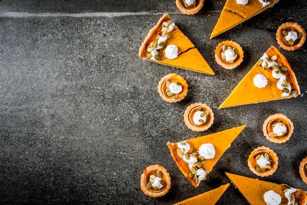 Pratos tradicionais de outono. dia das bruxas, ação de graças. conjunto de torta de abóbora picante e tortinhas de abóbora com chantilly & sementes de abóbora na mesa de pedra preta. vista do topo