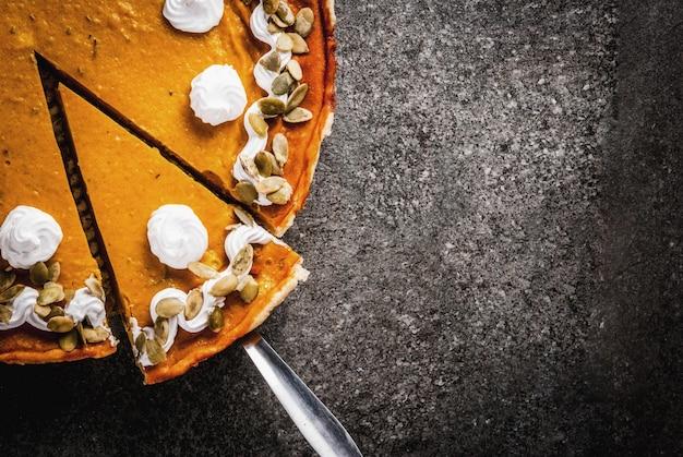 Pratos tradicionais de outono. dia das bruxas, ação de graças. tarte de abóbora picante fatiado com chantilly & sementes de abóbora na mesa de pedra preta. vista superior copyspace
