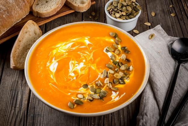 Pratos tradicionais de outono e inverno, sopa de abóbora quente e picante com sementes de abóbora, creme e baguete recém-assada, na velha mesa de madeira rústica,