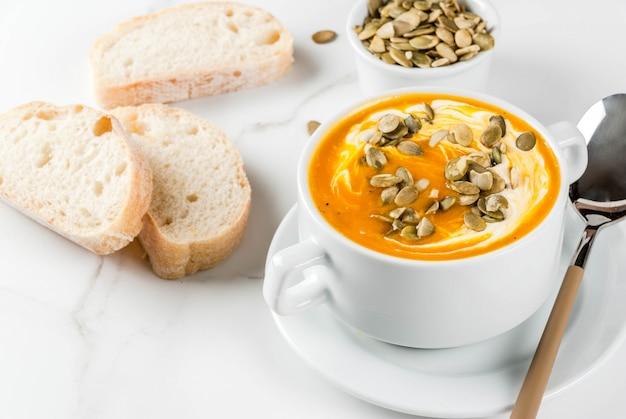 Pratos tradicionais de outono e inverno, sopa de abóbora quente e picante com sementes de abóbora, creme e baguete recém-assados, na mesa de mármore branca, copie o espaço