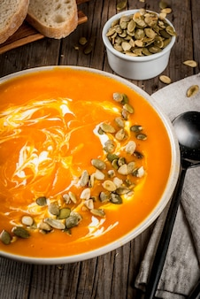 Pratos tradicionais de outono e inverno, sopa quente e picante de abóbora com sementes de abóbora, creme e baguete recém-assada