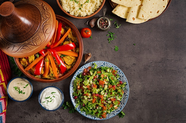 Pratos tradicionais de tajine, cuscuz e salada fresca na mesa de madeira rústica. legumes e carne de frango tagine