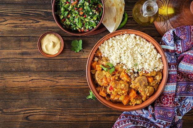 Pratos tradicionais tajine, cuscuz e salada fresca na mesa de madeira rústica.