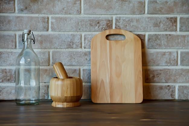 Pratos, utensílios de cozinha no interior da aconchegante área da cozinha em casa na bancada de madeira. cozinha ainda vida como pano de fundo para o projeto. conceito de conforto e relaxamento em casa. copie o espaço