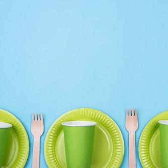 Pratos verdes com copos e talheres copiam espaço