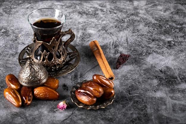 Prazer árabe datas em um mármore escuro com um copo de chá e alguns paus de canela