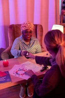 Prazer em conhecê-lo. cartomante rechonchudo afro-americano usando um anel enorme, encontrando um cliente