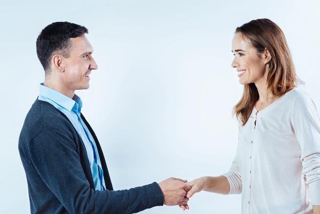 Prazer em conhecê-lo. vista lateral em um homem e uma mulher de aparência amigável se encontrando pela primeira vez e sorrindo amplamente enquanto apertam suas mãos.