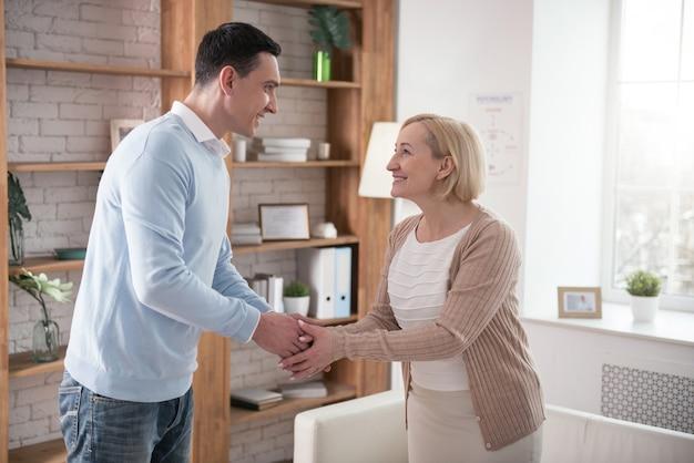 Prazer em conhecer. mulher sênior alegre e homem sorrindo enquanto apertava a mão