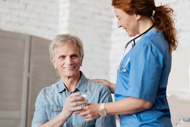 Prazer em ser útil. simpático cavalheiro idoso, que recebe um visitante do hospital que o vê regularmente e o ajuda em casa