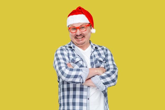 Prazer feliz homem moderno de meia idade no boné de papai noel vermelho, óculos e camisa quadriculada em pé com os braços cruzados e sorrindo, olhando para a câmera. interior, isolado em fundo amarelo.