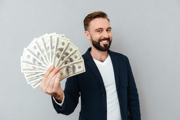 Prazer homem barbudo em roupas de negócios, mostrando dinheiro e olhando para a câmera sobre cinza
