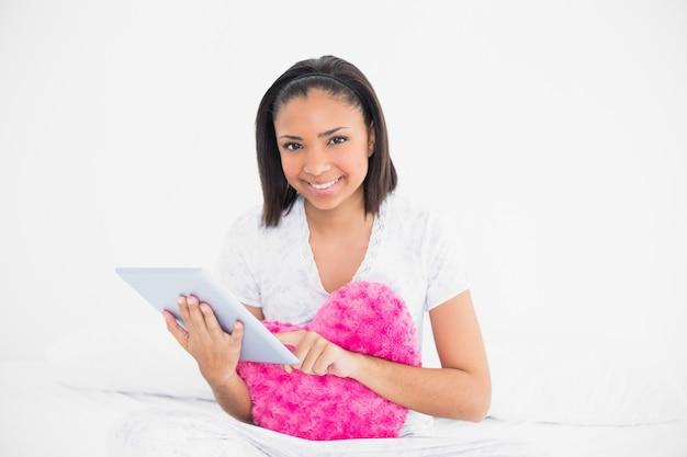 Prazer jovem modelo de cabelos escuros afago um travesseiro e usando um tablet pc