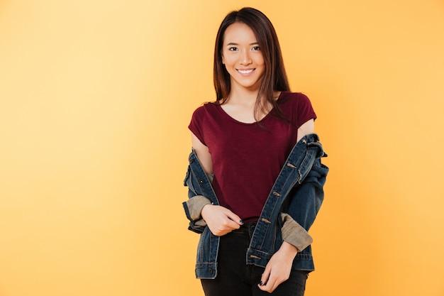 Prazer mulher asiática na jaqueta posando e olhando para a câmera