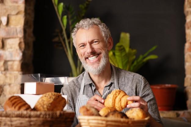 Prazer, trabalho. homem barbudo adulto feliz sorrindo com um croissant nas mãos, sentado perto de produtos assados prontos em uma padaria