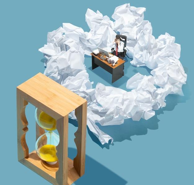 Prazo, papelada. vista de alto ângulo do escritório moderno criativo sobre fundo azul - coisas grandes e pequenos trabalhadores. trabalho de escritório, tarefa diária, problemas típicos e conceito de estilo de vida. colagem.