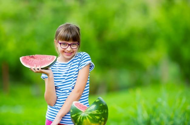Pré-adolescente no jardim segurando uma fatia de melancia, garota feliz, comendo melancia