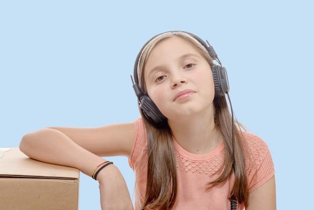 Pré-adolescente ouvindo música com fones de ouvido, fundo azul