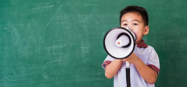 Pré-escola do jardim de infância de menino asiático com uniforme de estudante falando por um megafone contra o quadro