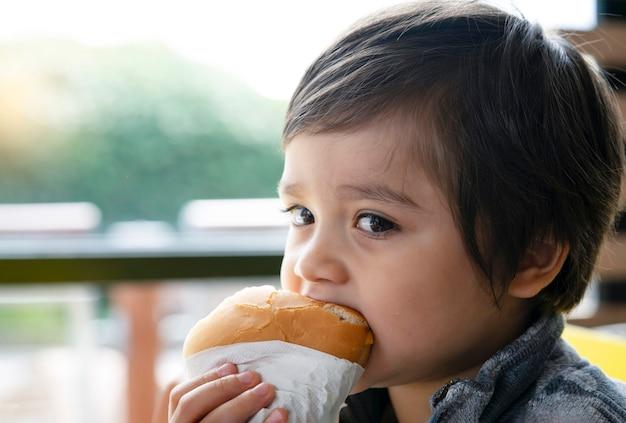 Pré-escolar garoto comendo hambúrguer sentado no café