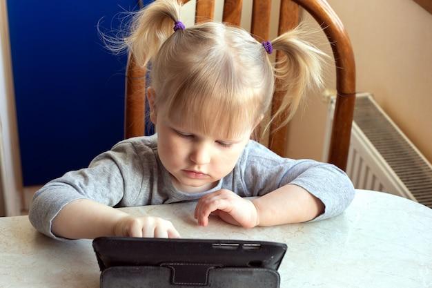 Pré-escolar menina caucasiana aprendendo on-line em um tablet digital.