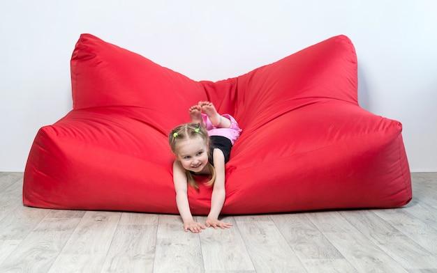 Pré-escolar menina deitada no grande sofá vermelho