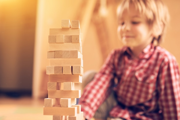 Pré-escolar menino bonitinho jogando em um jogo de mesa com blocos de madeira em casa