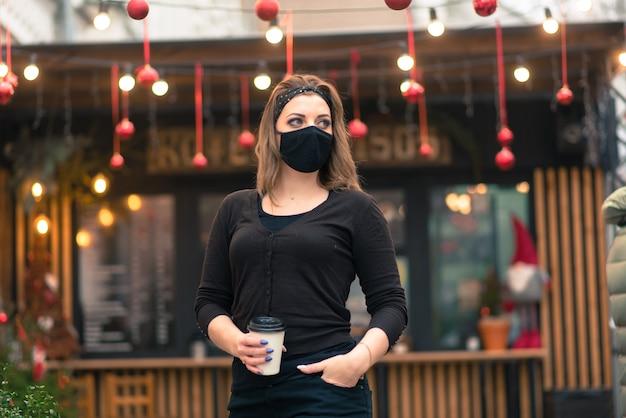 Precauções em locais públicos após o fim da quarentena. mulher jovem com máscara médica em um café